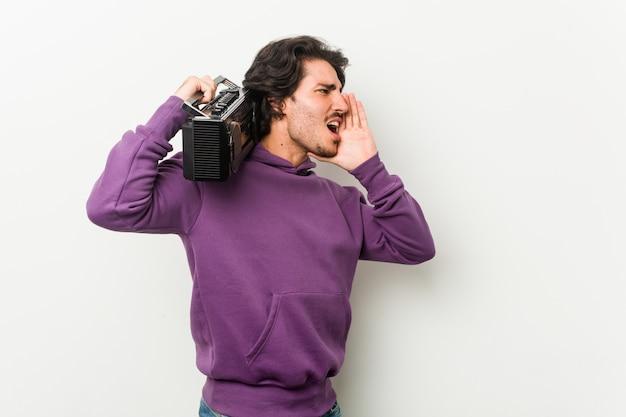 Junger städtischer mann, der einen guetto-blaster hält, der schreit und handfläche nahe geöffnetem mund hält.