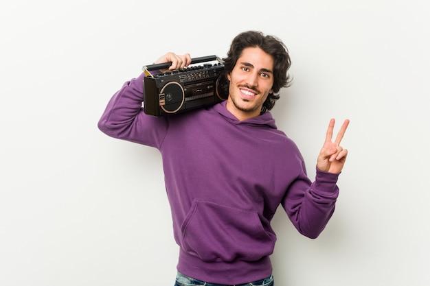 Junger städtischer mann, der einen guettoblaster froh und sorglos zeigt ein friedenssymbol mit den fingern hält.