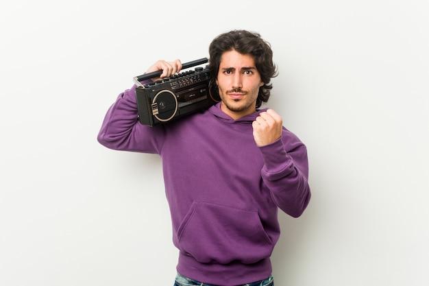 Junger städtischer mann, der einen guettoblaster zeigt faust zur kamera, aggressiver gesichtsausdruck hält.