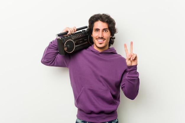 Junger städtischer mann, der einen guettoblaster zeigt nummer zwei mit den fingern hält.