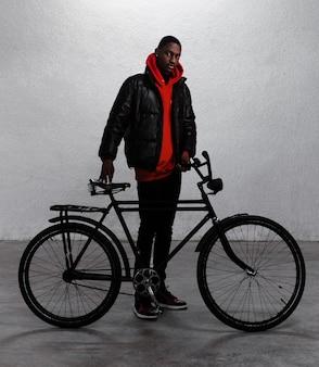 Junger städtischer mann, der mit seinem fahrrad geht
