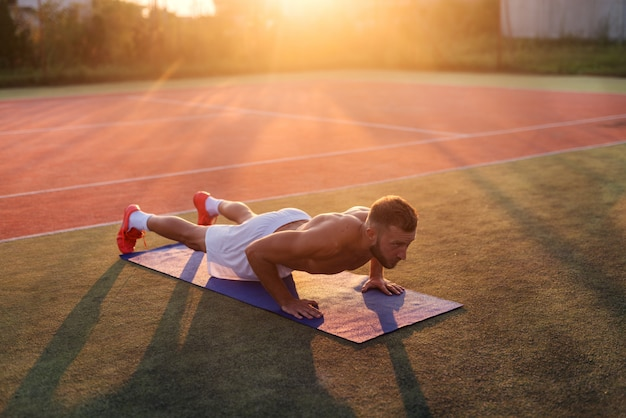 Junger starker engagierter mann, der liegestütze auf trainingsfeld tut. frühsommermorgen.