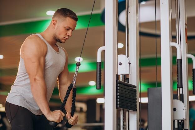 Junger starker mann, der an der turnhalle trainiert