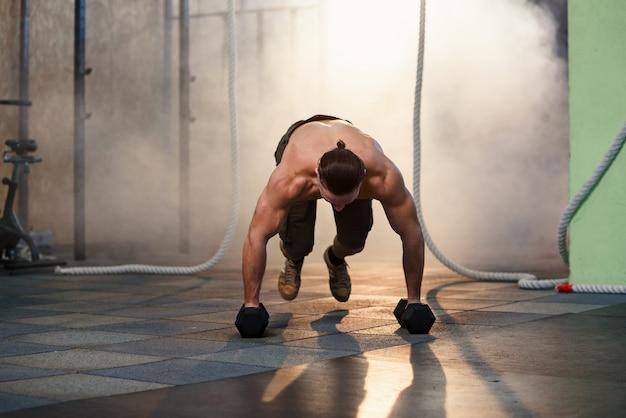 Junger starker mann, der liegestütze mit hanteln während des trainings im fitnessstudio tut.