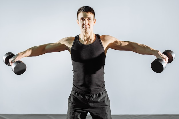 Junger starker mann, der mit dummköpfen in der turnhalle trainiert.