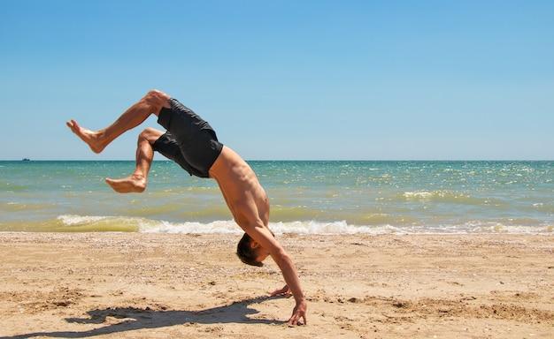 Junger starker mann in ausgezeichneter körperlicher verfassung steht am strand in der nähe des meeres