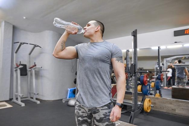 Junger starker muskulöser mann in trinkwasser der turnhalle von der flasche