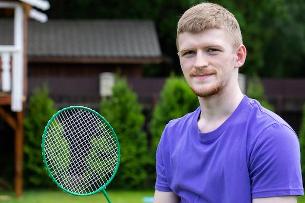 Junger starker sport kaukasischer mann, der mit badmintonschläger auf grüner natur aufwirft. konzept des amateurspiels badminton, sommer outdoor-aktivitäten.