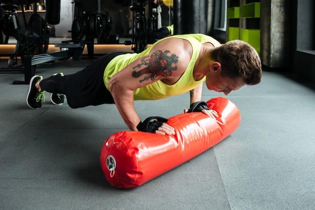 Junger starker sportler, der liegestütze tut und boxsack benutzt