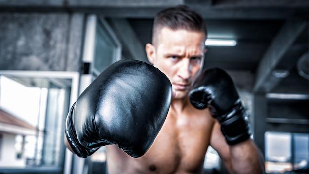 Junger starker sportmannboxer machen übungen im fitnessstudio