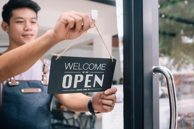 Junger startkaffeecafébesitzer öffnen und begrüßen kunden.