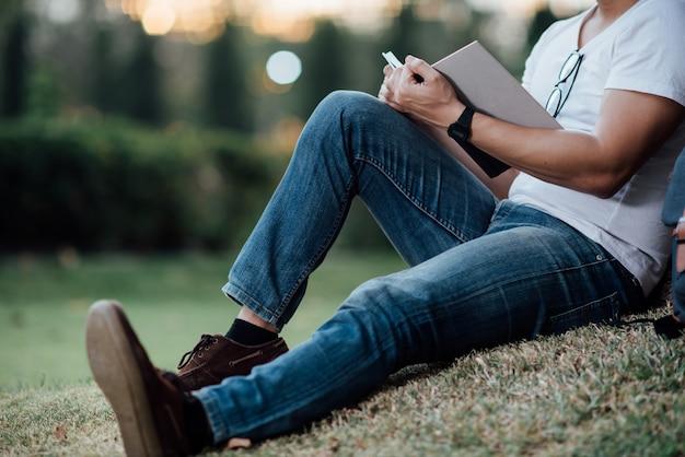 Junger stattlicher mann, der auf grünem gras sich entspannt