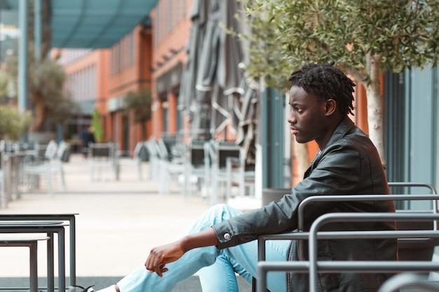 Junger stilvoller afroamerikanischer kerl, der auf einem stuhl auf der straße in lyon in frankreich sitzt