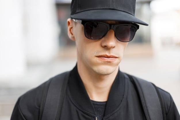 Junger stilvoller ernsthafter mann-hipster in einer schwarzen basketballkappe in einer modischen schwarzlicht-herbstjacke in sonnenbrille steht auf der straße