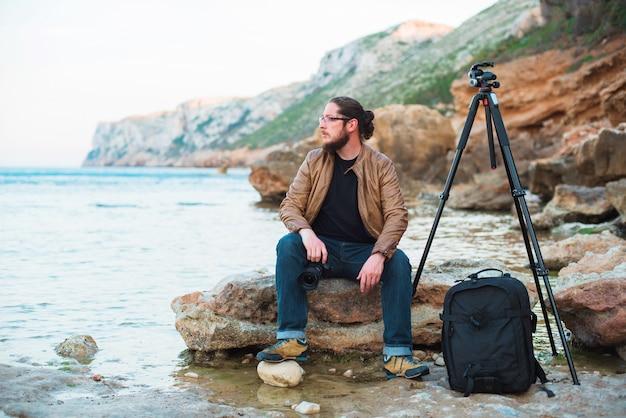 Junger stilvoller fotograf, der auf felsen sitzt und meer mit kamera in den händen betrachtet