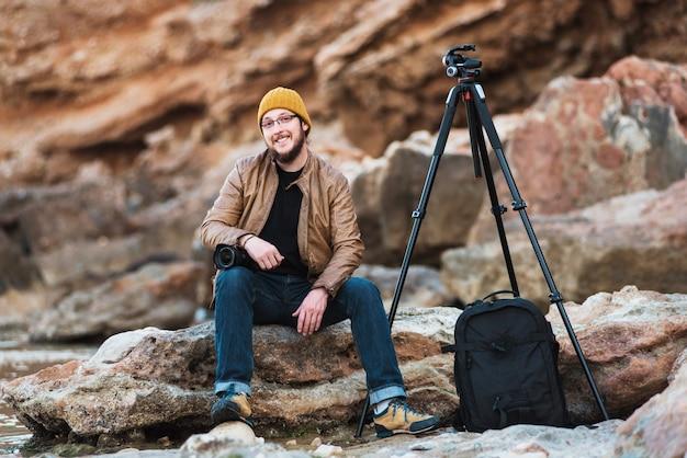 Junger stilvoller fotograf mit kamera in den händen, die auf dem felsen und dem lächeln sitzen