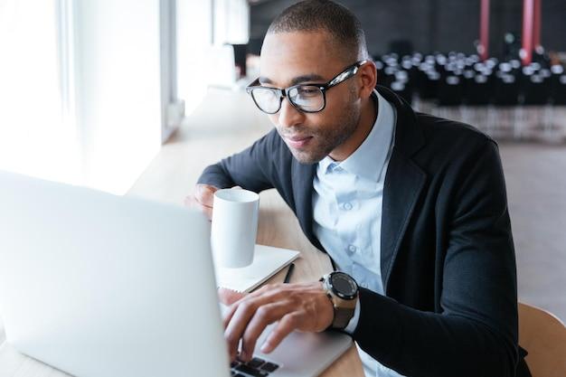 Junger stilvoller geschäftsmann, der mit laptop-computer im büro arbeitet