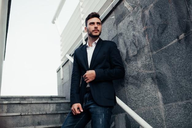 Junger stilvoller geschäftsmannmann mit einem bart in einem modernen anzug und in den jeans.