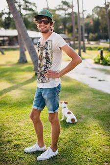Junger stilvoller hipster-mann, der mit hund im tropischen strand geht und spielt