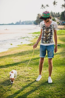 Junger stilvoller hipster-mann, der spielt, spielt welpenwelpe jack russell, tropischer strand, cooles outfit, spaß, sonnig