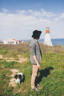Junger stilvoller hipster-mann im hut, der mit hund in der landschaft geht