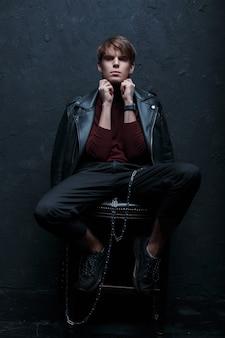 Junger stilvoller hipster-mann in einer vintage-lederjacke in rotem golf in schwarzen jeans in turnschuhen mit einer metallsilberkette, die die kamera in einem dunklen studio nahe der wand aufwirft und betrachtet. stilvoller typ