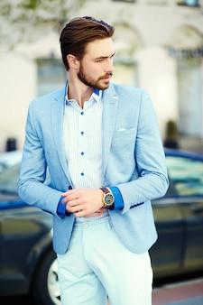 Junger stilvoller hübscher mann im anzug in der straße