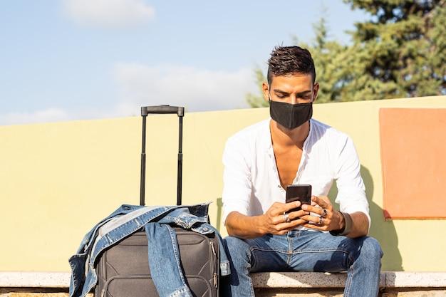 Junger stilvoller kaukasischer mannreisender mit einer schwarzen covid-schutzmaske unter verwendung des smartphones