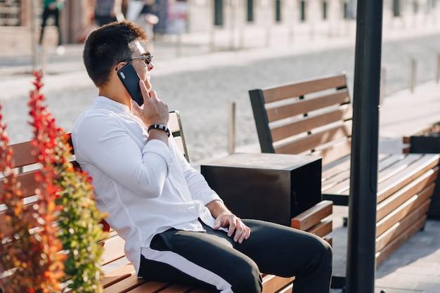 Junger stilvoller kerl im hemd mit telefon auf bank am sonnigen warmen tag draußen