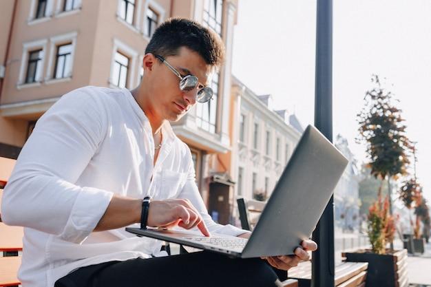 Junger stilvoller kerl im hemd mit telefon und notizbuch auf bank am sonnigen warmen tag draußen, freiberuflich