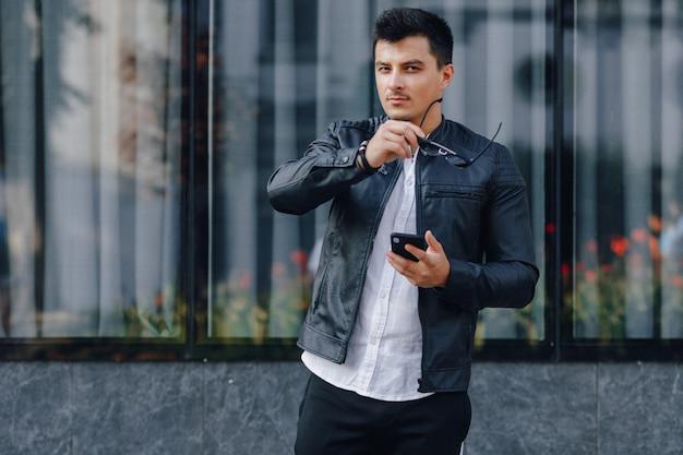 Junger stilvoller kerl in den gläsern in der schwarzen lederjacke mit telefon auf glashintergrund