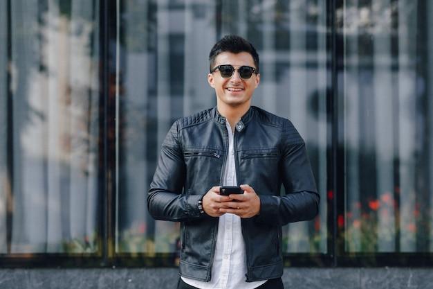 Junger stilvoller kerl in den gläsern in der schwarzen lederjacke mit telefon auf glasoberfläche