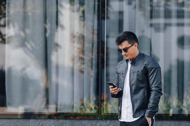 Junger stilvoller kerl in den gläsern in der schwarzen lederjacke mit telefon