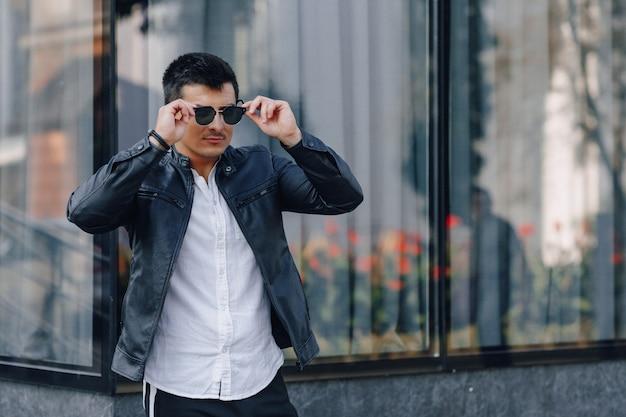 Junger stilvoller kerl in den gläsern in der schwarzen lederjacke