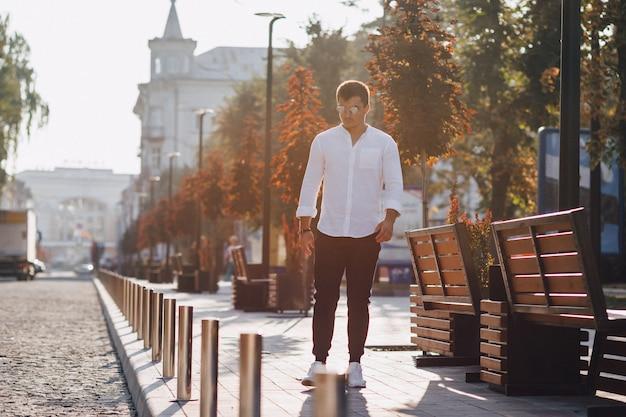 Junger stilvoller kerl in einem hemd, das eine europäische straße an einem sonnigen tag geht