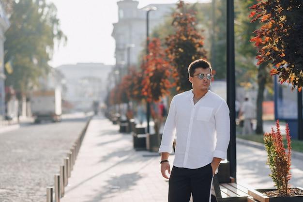 Junger stilvoller kerl in einem hemd gehend hinunter eine europäische straße an einem sonnigen tag
