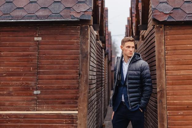 Junger stilvoller kerl mit einem monumentalen gesicht geht in eine kühle stadt nahe den hölzernen und steinwänden