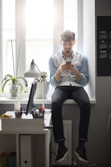 Junger stilvoller mann, der auf dem fenster mit telefon in den händen sitzt