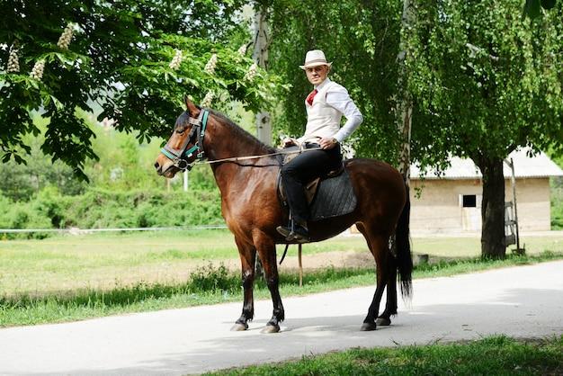 Junger stilvoller mann, der das reiten eines pferds auf landschaft nimmt