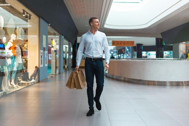 Junger stilvoller mann, der in einem einkaufszentrum mit umweltfreundlichen einkaufstaschen in der hand mit waren und kleidung spaziert. verkauf, rabatt ausverkauftes konzept. saisonaler ausverkauf.