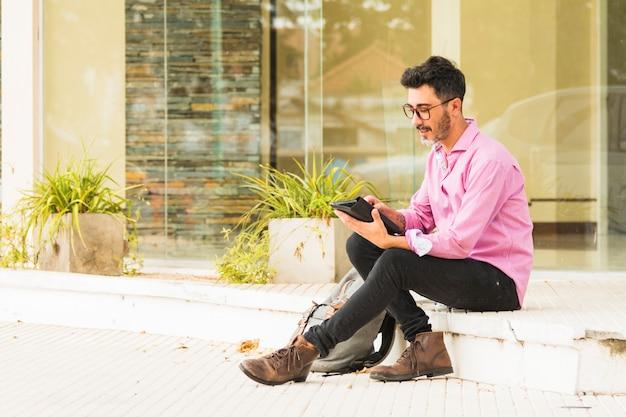 Junger stilvoller mann, der mit seinem rucksack unter verwendung der digitalen tablette sitzt