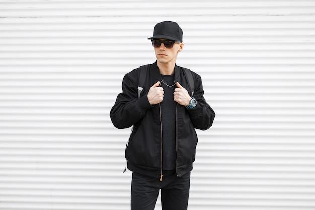 Junger stilvoller mann hipster in einer schwarzen mütze in sonnenbrille in stilvollen jeans in einer schwarzen bomberjacke mit einem rucksack auf seinen schultern steht auf der straße in der nähe einer weißen metallwand. ernsthafter modetyp.