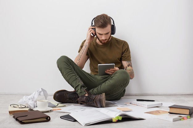 Junger stilvoller mann hört musik mit kopfhörern, hält modernen tablet-computer, kommuniziert mit freunden oder verwandten online