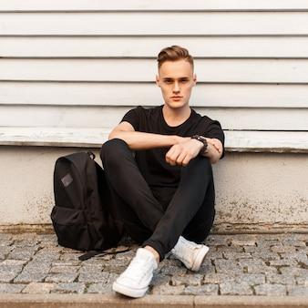 Junger stilvoller mann im schwarzen hemd und in den weißen schuhen mit einem rucksack sitzt nahe holzwand