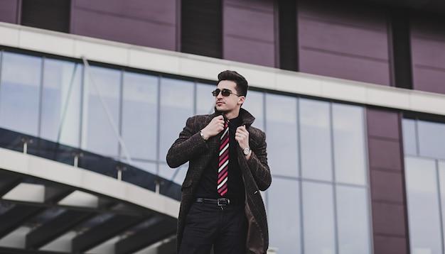 Junger stilvoller mann im trendigen mantel, der in stadtstraße aufwirft