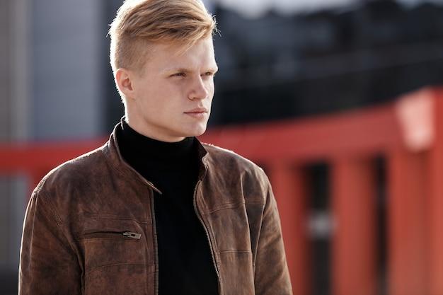 Junger stilvoller mann in brauner jacke schaut weg, während er im freien steht. streetstyle