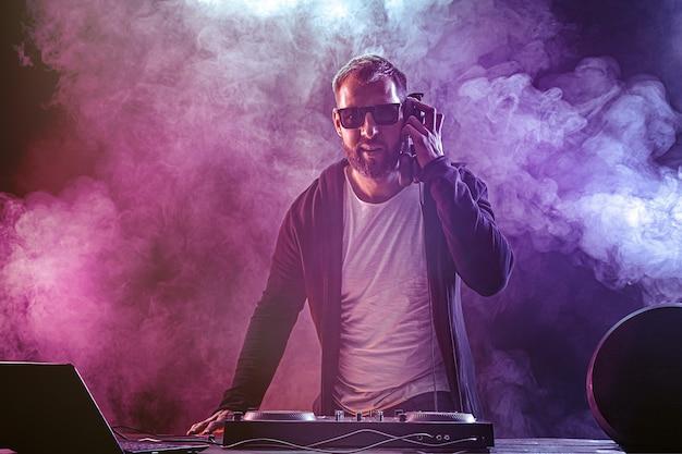 Junger stilvoller mann in den gläsern, die hinter mischender konsole auf farbigem rauchstudio aufwerfen