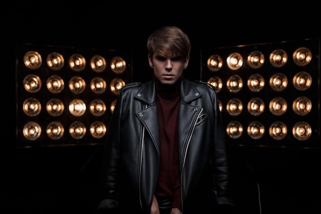 Junger stilvoller mann in der kühlen schwarzen lederjacke im roten golf in der stilvollen hose, die in einem dunklen studio vor dem hintergrund der elektrischen leuchtend orange glühbirnen aufwirft. attraktiver star