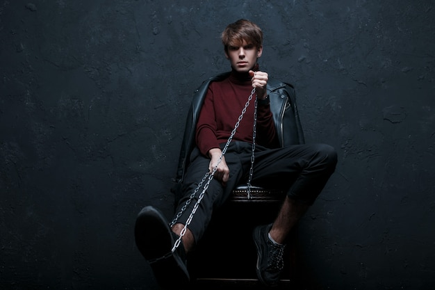 Junger stilvoller mann in einer jacke in einem vintage-burgundergolf in trendigen jeans und turnschuhen mit einer metallkette sitzt auf einem stuhl und schaut in die kamera im studio gegen die schwarze wand. netter kerl