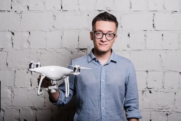 Junger stilvoller mann in gläsern mit quadcopter-drohne auf einer grauen backsteinmauer